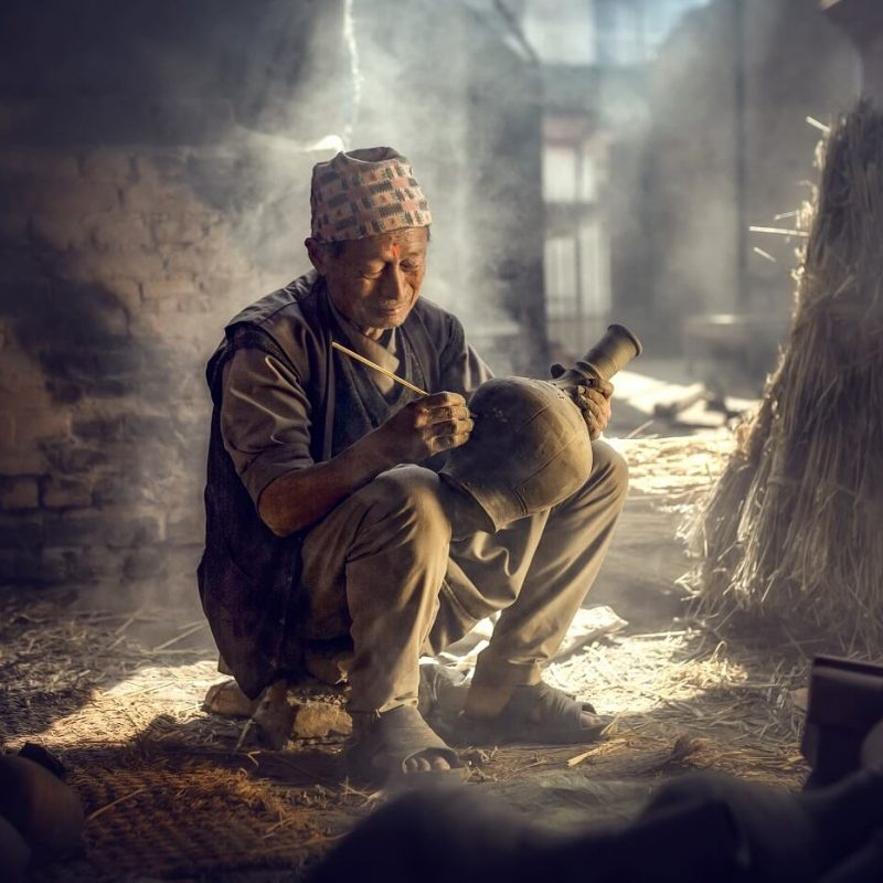 The old man is painting in a clay pot in Durbar square near old hindu temples.